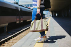 Donna che tiene una borsa ad una stazione ferroviaria Fotografie Stock Libere da Diritti