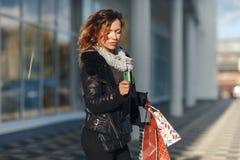Donna che tiene una carta di credito e che per mezzo del telefono cellulare per l'acquisto online fotografia stock libera da diritti