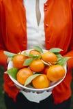 Donna che tiene una ciotola di tangerinesFemale che tiene una ciotola con i mandarini freschi fotografia stock libera da diritti