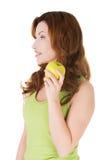Donna che tiene una mela e che guarda da qualche parte Fotografie Stock
