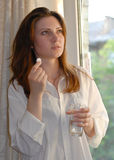 Donna che tiene una pillola e un vetro di acqua Fotografie Stock