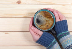 Donna che tiene una tazza di caffè sui precedenti di legno fotografia stock