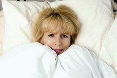Donna che tira coperta verso il suo fronte nel timore Immagine Stock