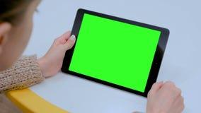 Donna che tocca l'esposizione verde dello schermo attivabile al tatto dello schermo della compressa digitale nera a casa video d archivio