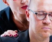 Donna che tormenta un uomo sul posto di lavoro Immagine Stock