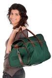 Donna che trasporta un sacchetto di fine settimana sopra la sua spalla Immagini Stock Libere da Diritti