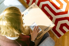Donna che unboxing disimballando Amazon COM inscatola Fotografie Stock