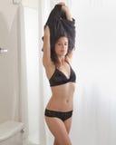 Donna che undressing nella stanza da bagno Immagini Stock