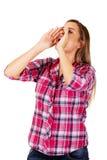 Donna che urla facendo uso delle sue mani come megafono fotografia stock