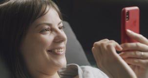 Donna che usa il suo cellulare sul divano archivi video
