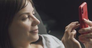 Donna che usa il suo cellulare sul divano stock footage