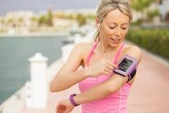Donna che usando allenamento app sul suo smartphone fotografia stock