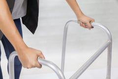 Donna che usando camminatore su fondo bianco fotografie stock