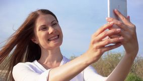 Donna che usando cellulare contro il cielo blu Foto di presa femminile sorridente del selfie sul cellulare al rallentatore video d archivio