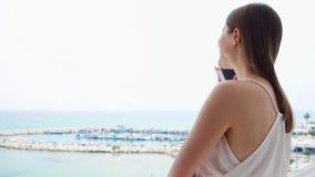 Donna che usando cellulare sul balcone Femmina sulla vacanza che parla con l'amico tramite cellulare al rallentatore video d archivio