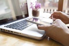Donna che usando computer portatile e telefono cellulare all'acquisto online e paga dalla carta di credito Fotografia Stock Libera da Diritti