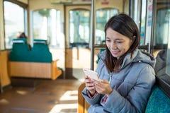 Donna che usando il compartimento del treno dell'interno del cellulare Fotografia Stock