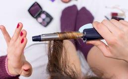 Donna che usando il ferro di arricciatura sui suoi capelli Immagini Stock Libere da Diritti
