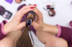 Donna che usando il ferro di arricciatura sui suoi capelli Fotografia Stock
