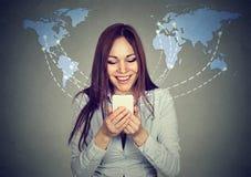 Donna che usando Internet di lettura rapida dello smartphone sul fondo mondiale della mappa Immagine Stock Libera da Diritti