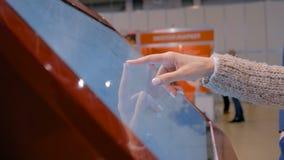 Donna che usando l'esposizione interattiva dello schermo attivabile al tatto alla mostra di tecnologia stock footage