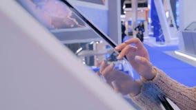 Donna che usando l'esposizione interattiva dello schermo attivabile al tatto alla mostra di tecnologia video d archivio