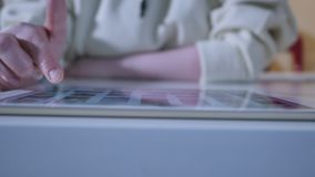 Donna che usando l'esposizione interattiva dello schermo attivabile al tatto alla mostra urbana - scorrimento e toccare concetto  stock footage