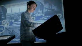 Donna che usando l'esposizione interattiva dello schermo attivabile al tatto al museo di storia moderna archivi video