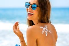 Donna che usando la crema del sole sulla spiaggia Fotografie Stock