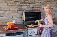 Donna che usando la griglia del barbecue Fotografie Stock Libere da Diritti
