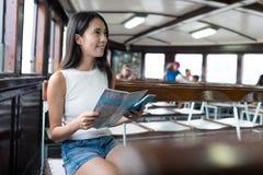Donna che usando la mappa di carta della città e prendendo traghetto nella città di Hong Kong fotografia stock