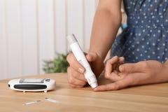 Donna che usando la penna della lancetta alla tavola fotografia stock
