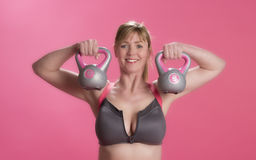 Donna che usando le campane del bollitore per esercitarsi Fotografie Stock Libere da Diritti