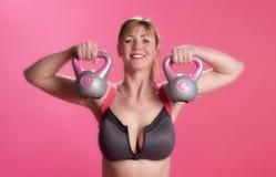 Donna che usando le campane del bollitore per esercitarsi Immagini Stock Libere da Diritti