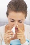 Donna che usando le gocce nasali Fotografie Stock Libere da Diritti