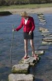 Donna che usando le pietre facenti un passo per attraversare un fiume Immagini Stock Libere da Diritti