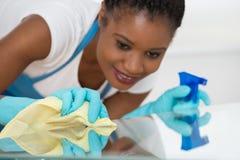 Donna che usando spruzzo per pulire scrittorio di vetro immagine stock