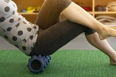Donna che usando un rotolo di schiuma sulla sua gamba per allentare tensione Immagine Stock