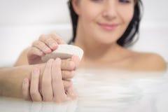 Donna che usando una pietra pomice per esfoliare i suoi piedi Fotografia Stock