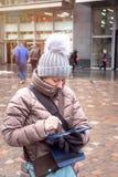 Donna che usando una tavola digitale all'aperto sotto la pioggia fotografia stock libera da diritti