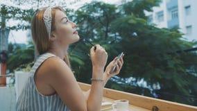 Donna che utilizza app sullo smartphone nel caffè Ragazza che decolla i suoi vetri archivi video