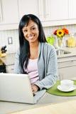 Donna che utilizza calcolatore nella cucina Fotografia Stock