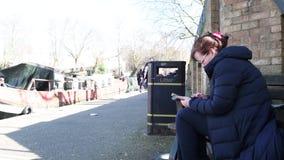 Donna che utilizza compressa astuta in poco messaggio di scrittura di Venezia Londra video d archivio