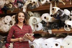 Donna che utilizza compressa nel magazzino di stoccaggio del tessuto, ritratto Immagine Stock