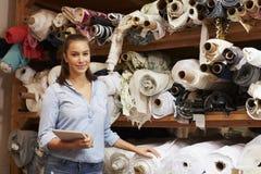 Donna che utilizza compressa nel magazzino di stoccaggio del tessuto, ritratto Fotografia Stock