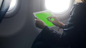 Donna che utilizza compressa nell'aeroplano luminoso leggero video d archivio