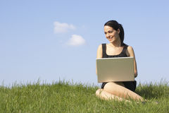Donna che utilizza computer portatile all'aperto nella campagna di estate Fotografia Stock