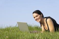 Donna che utilizza computer portatile all'aperto nella campagna di estate Immagini Stock