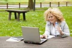 Donna che utilizza computer portatile nell'acqua della bevanda e della sosta Immagini Stock