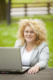Donna che utilizza computer portatile nell'ufficio aperto Immagini Stock